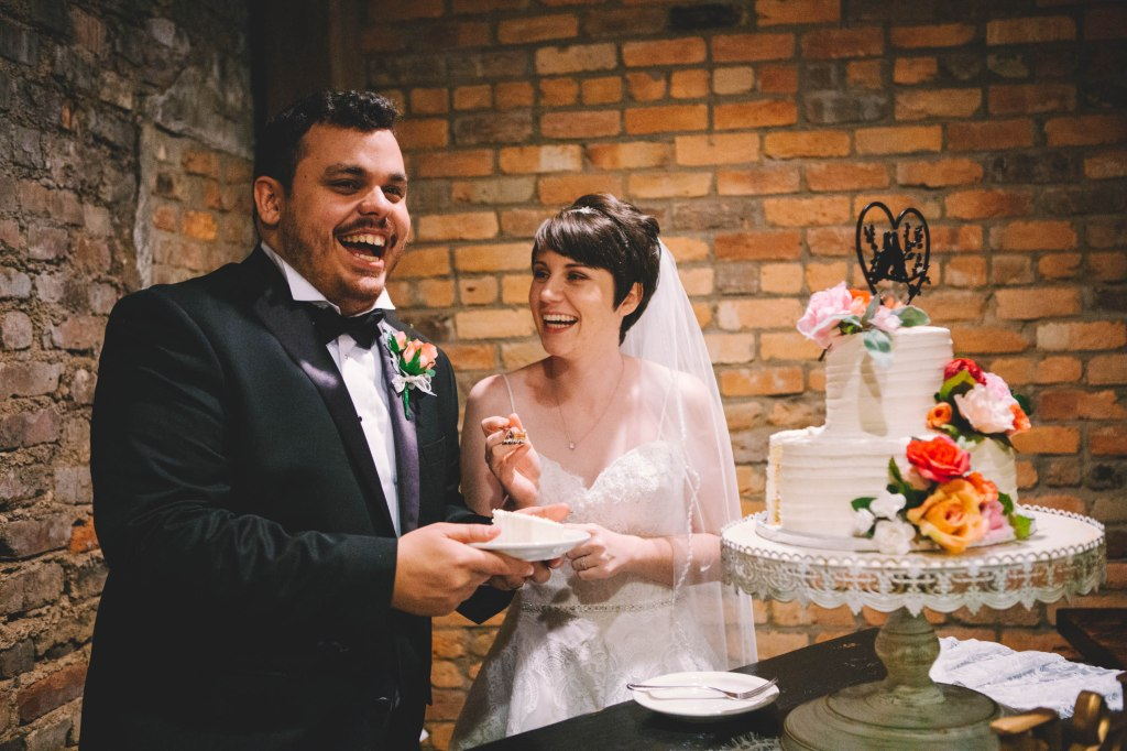 Couple laughing and smiling after they've cut a piece of their wedding cake.