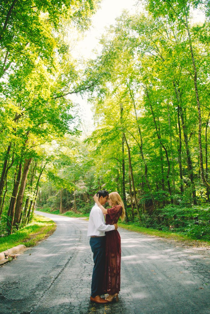 Couple gazing at each other on street in a wooded area.