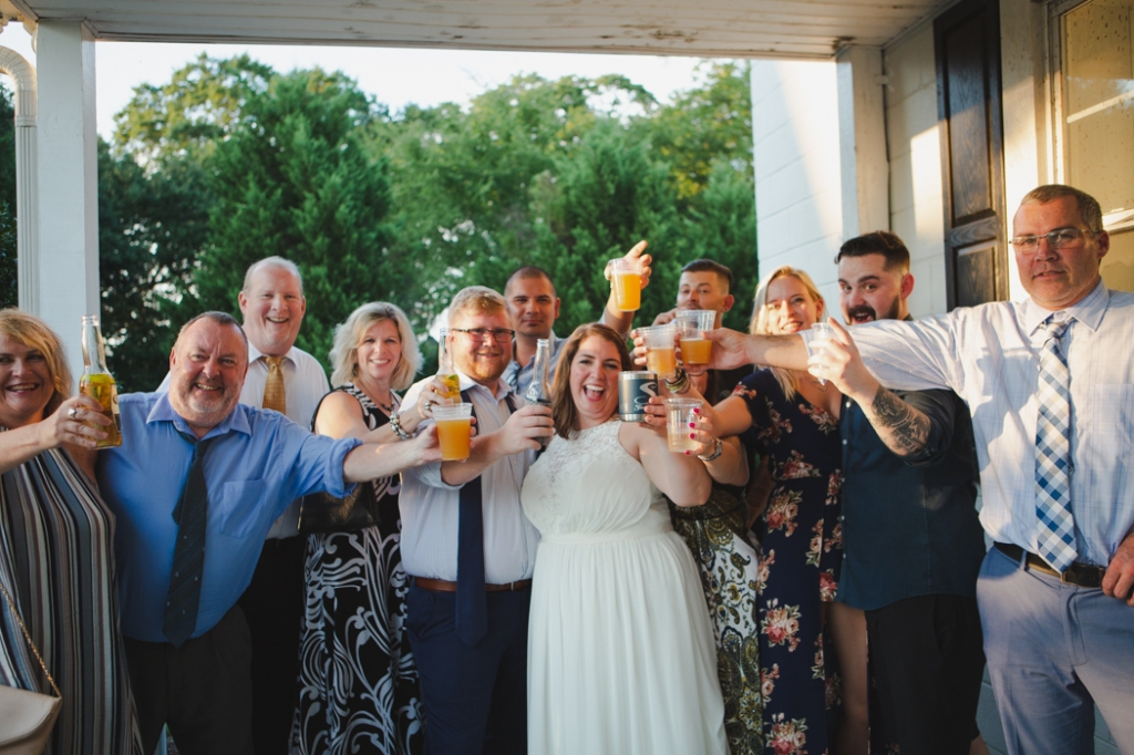 Cheersing group photo of friends surrounding a bride and groom.