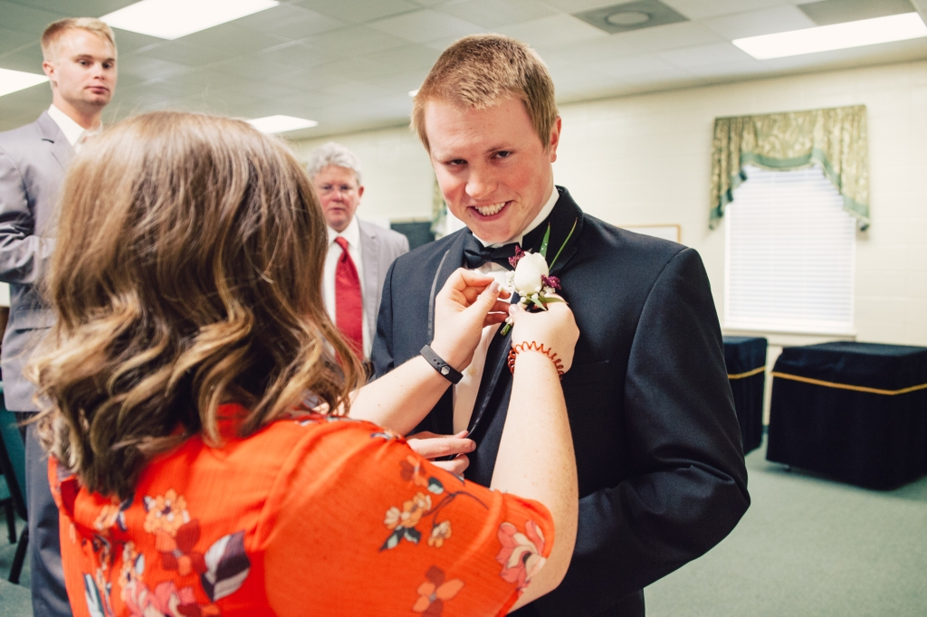 Groom making a silly face while the wedding planner adjusts his boutonnière.