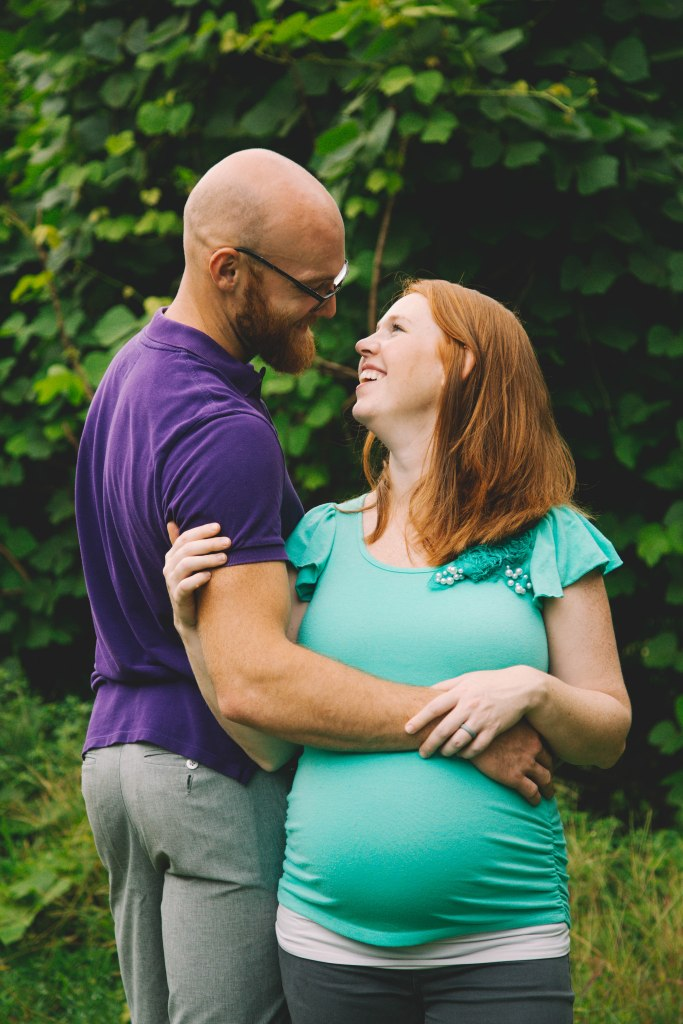 Maternity shot of a husband and wife holding each other and smiling.