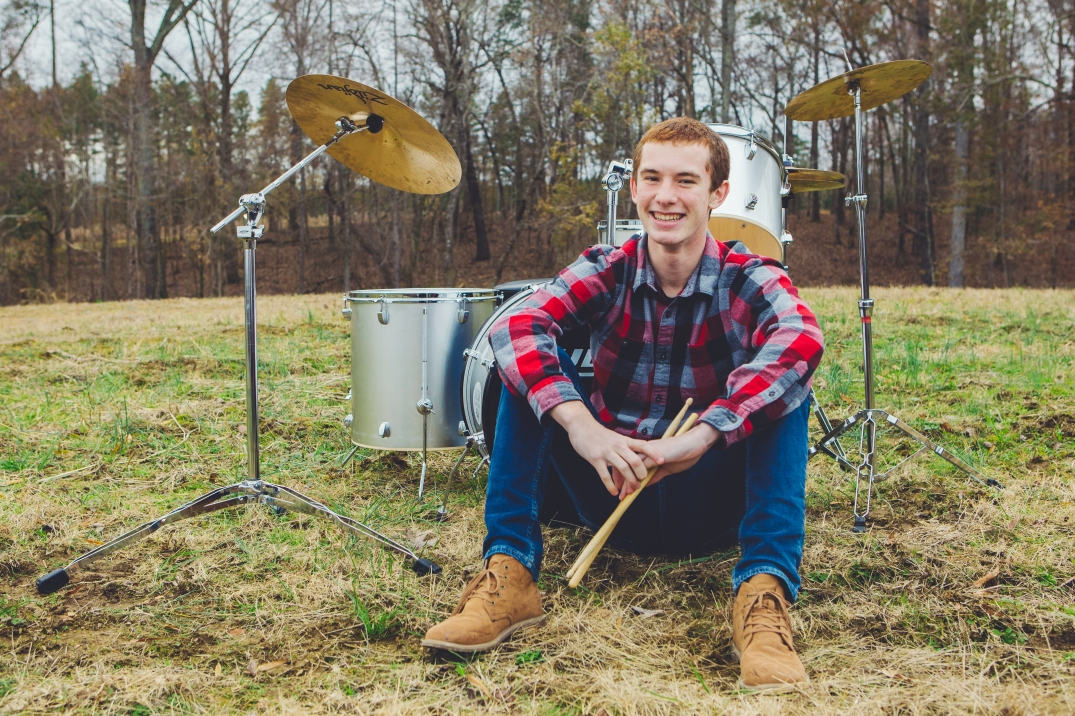 Portrait of a senior by his drum set.