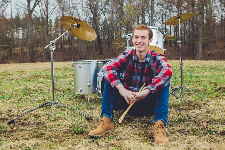 Portrait of a senior by his drum set.