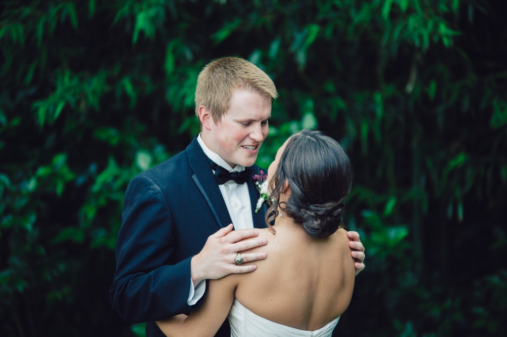 Groom staring lovingly at his bride while he hugs her.