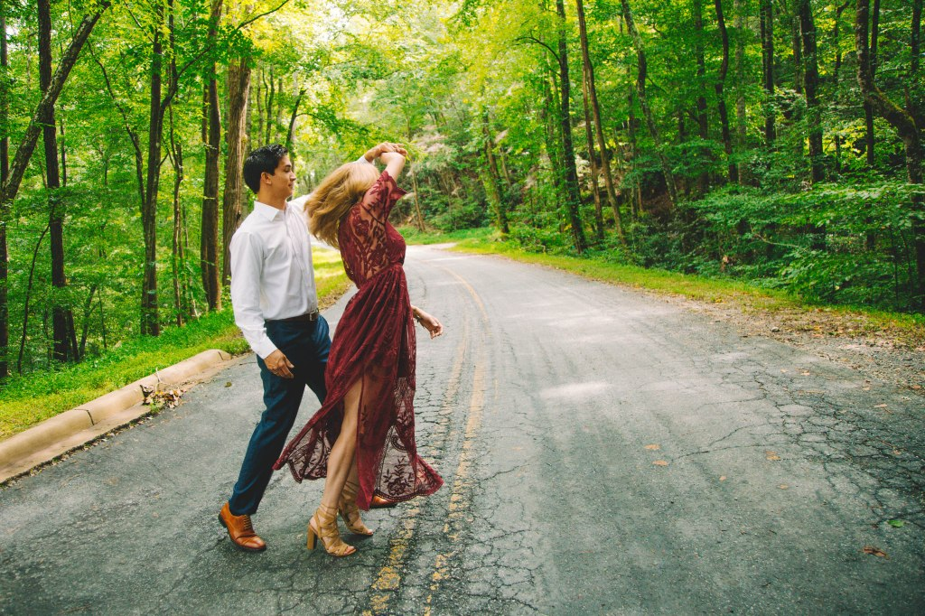 Couple dancing on street in a wooded area.
